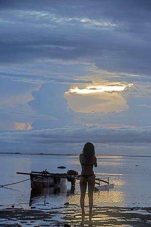 Beachouse girl clouds sunset outrigger over water