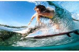 Surfer at Fiji Beachouse seen through a crystal clear wave